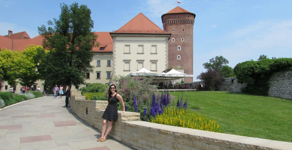 Kate Storm in a black dress standing in the courtyard of Wawel Castle--definitely stop by here during your 2 day Krakow Itinerary!