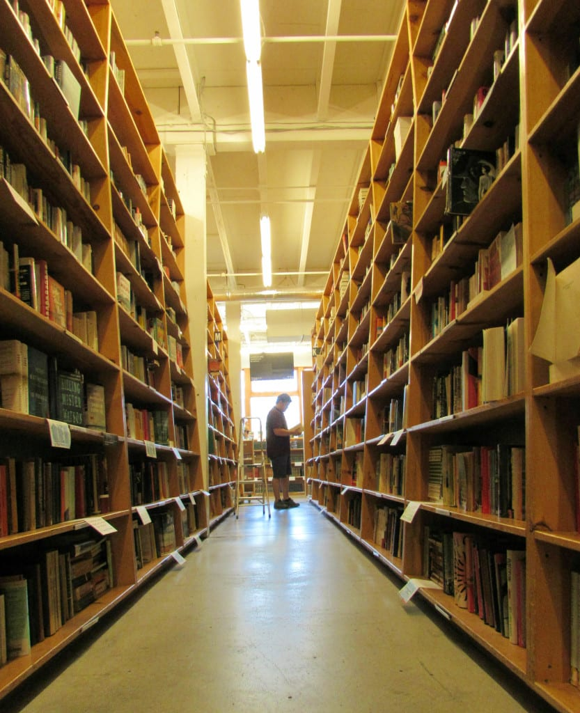 Jeremy standing at the end of an aisle in Powell's City of Books, Portland, Oregon--Portland is among the best US weekend trips to take!