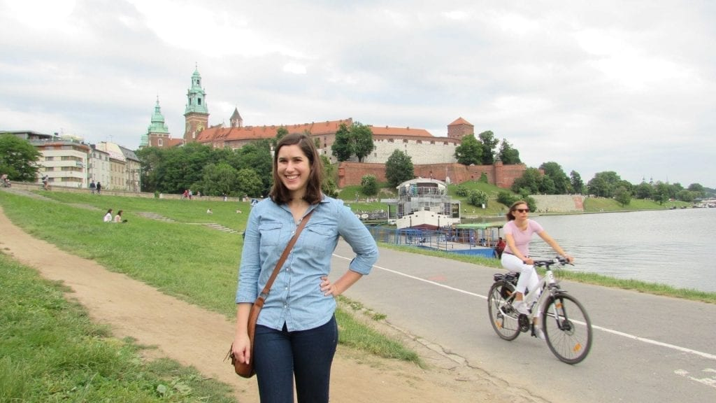 Kate Storm standing in front of Wawel Castle on the banks of the Vistula River when visiting Krakow Poland