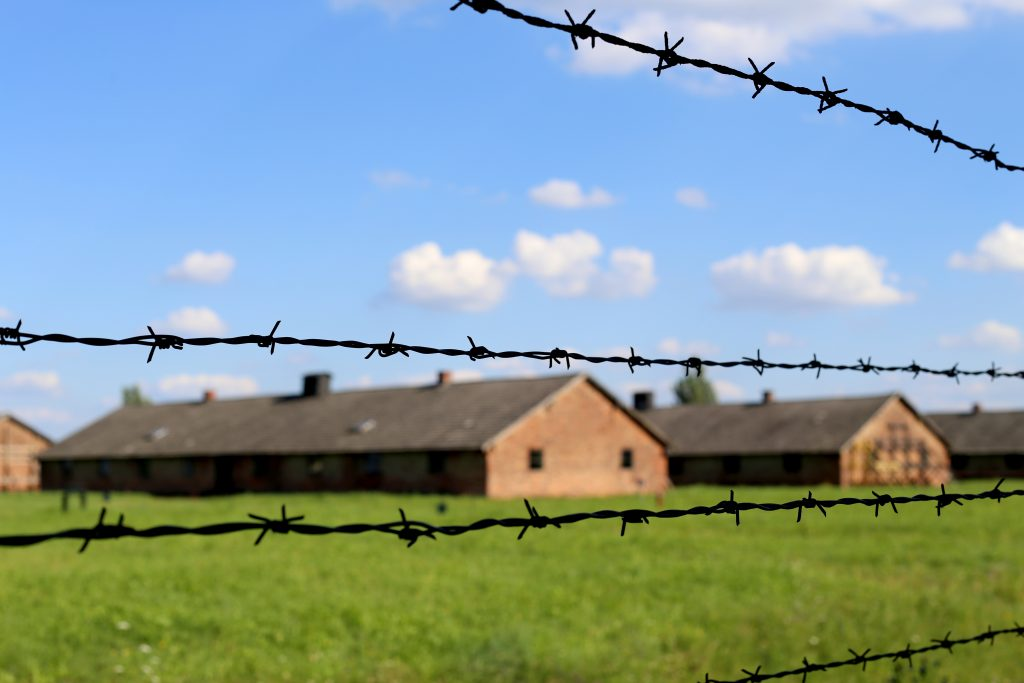 barracks of birkenau concentration camp as seen through barbed wire fence