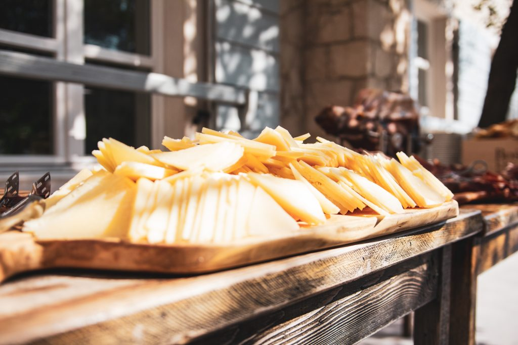 slices of pag cheese set on a platter outside on a wooden table on pag island, one of the best day trips from zadar croatia