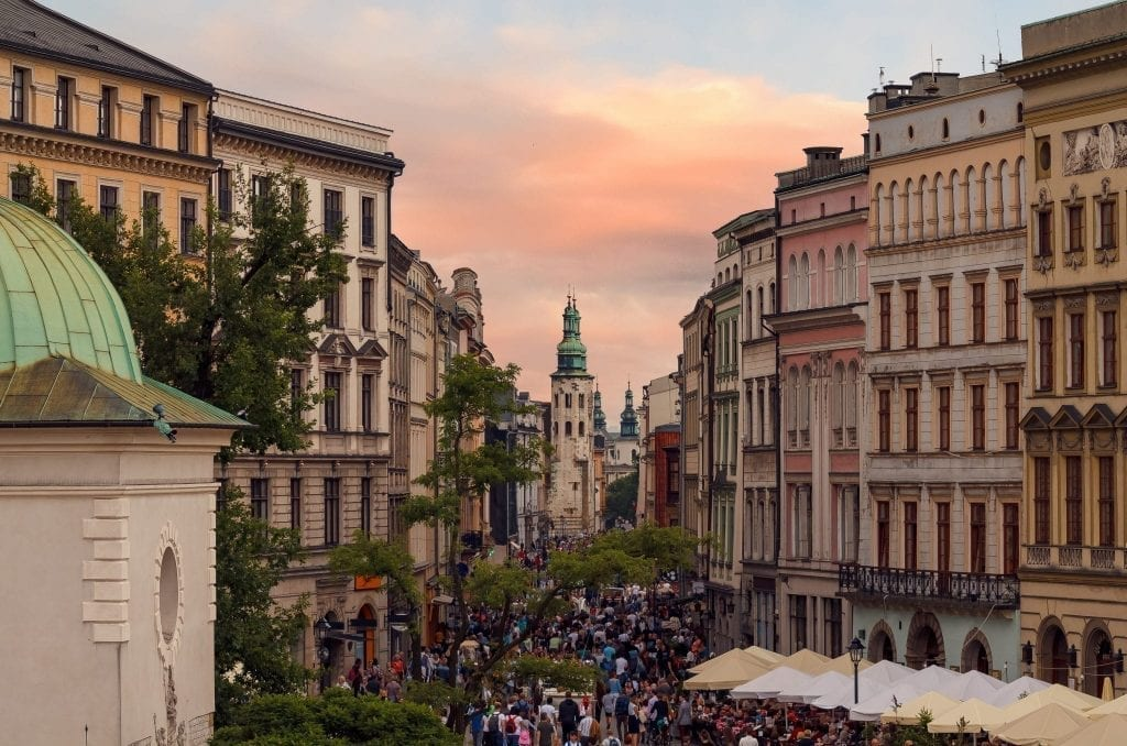 Crowded Grodzka Street in Krakow Poland near sunset with buildings lining either side of the photo