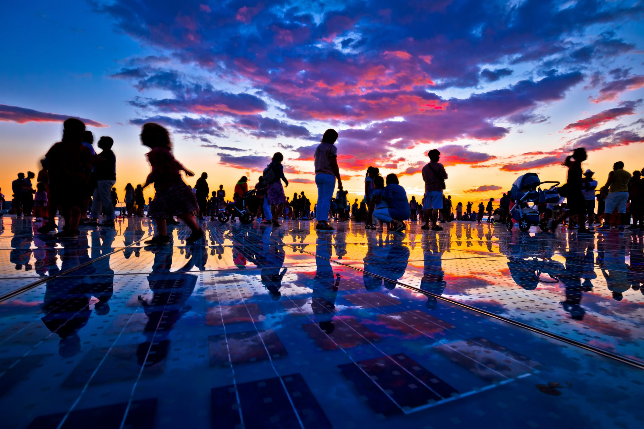 crowd of people at sunset in zadar croatia during a purple and orange sunset