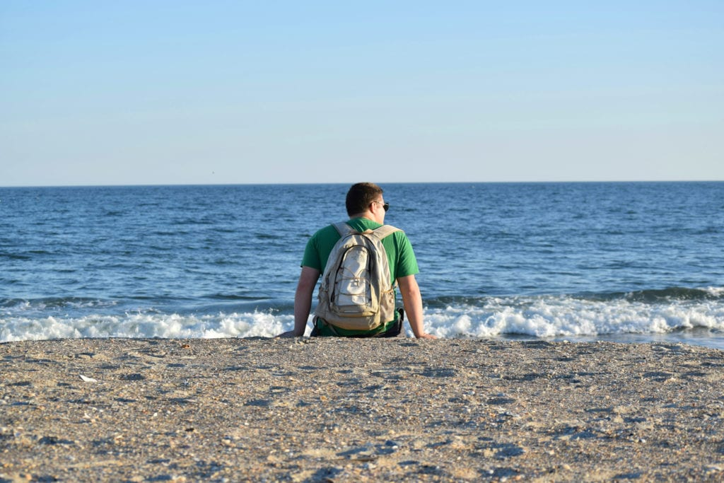 Jeremy Storm sitting on the beach at Fort Macon State Park North Carolina wearing a backpack and overlooking the ocean