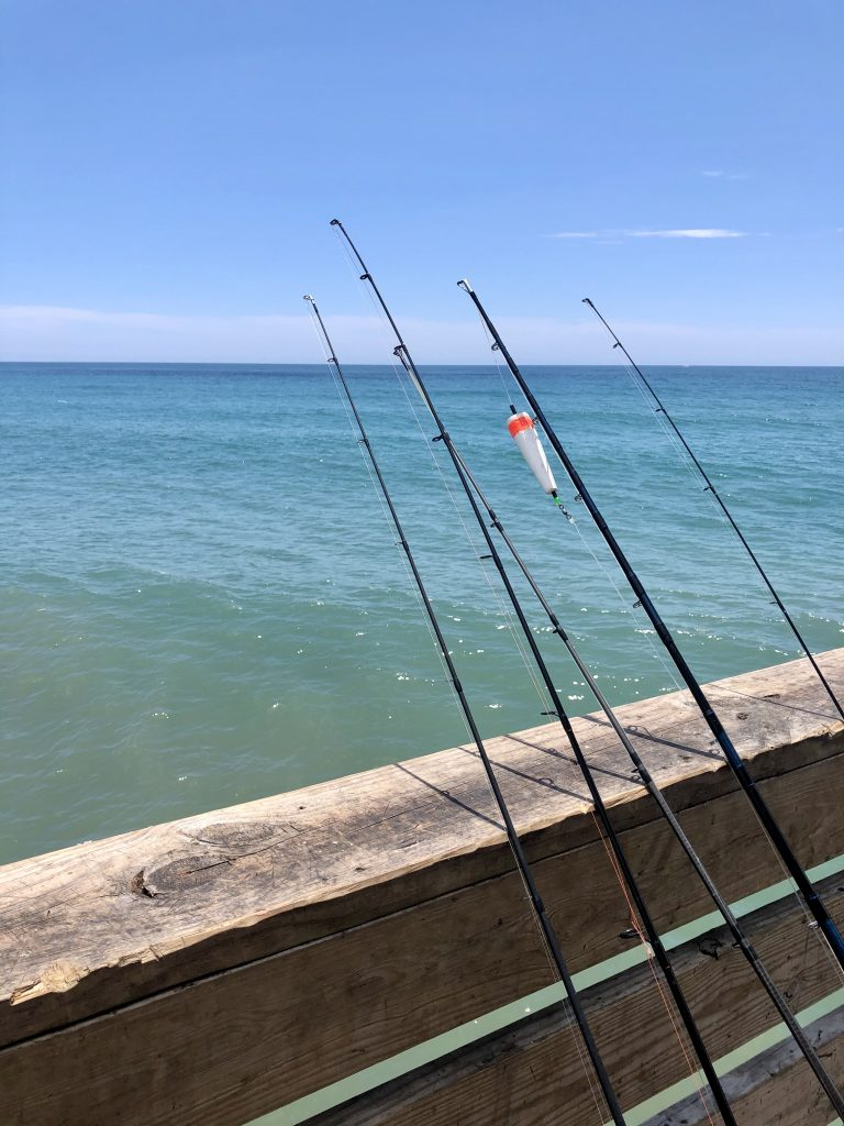 fishing poles leaning against oceanana pier, one of the best places to visit in atlantic beach north carolina
