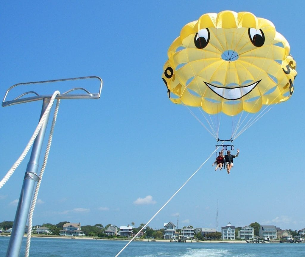 Kate Storm and Jeremy Storm seated below a bright yellow parasail that is over the Bogue Sound. Parasailing is one of the fun things to do in Atlantic Beach NC