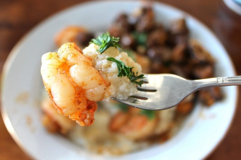 Plate of shrimp and grits with a bite on a fork being held in the foreground
