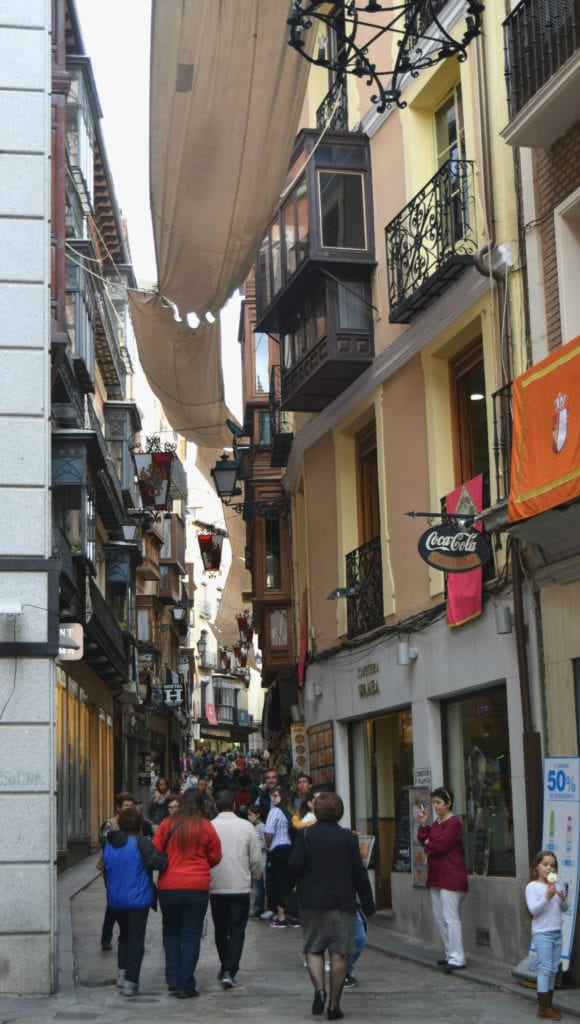 Small street in Toledo Spain with a yellow building on the right and a crowd below