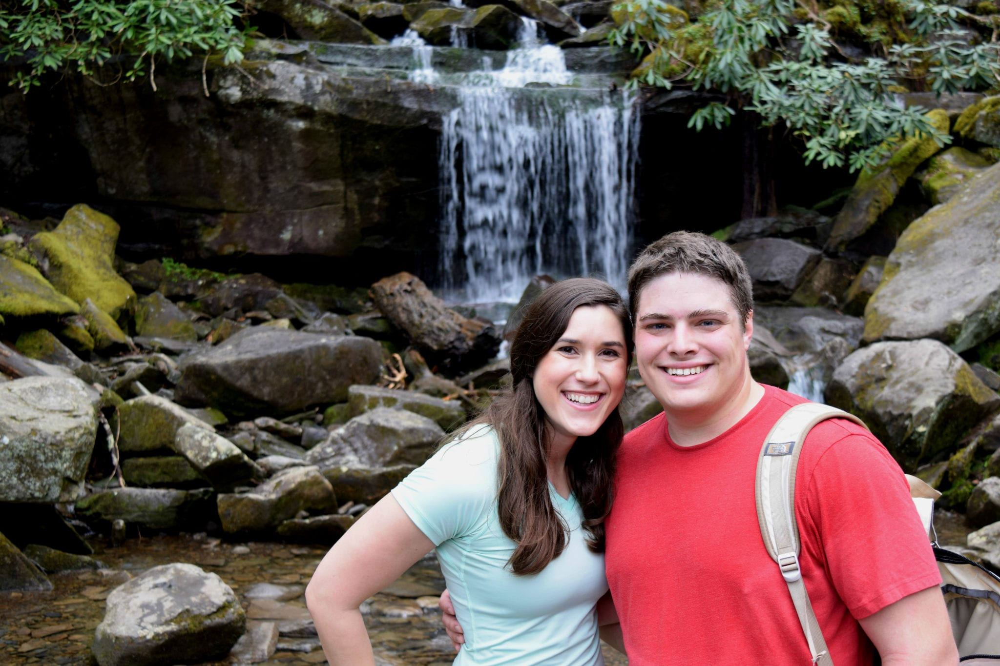 Kate and Jeremy standing in front of a small waterfall in Great Smoky Mountains National Park. Kate is wearing a blue shirt and Jeremy red. GSMNP is easily accessible from Asheville, one of the best cities for weekend getaways in the USA!