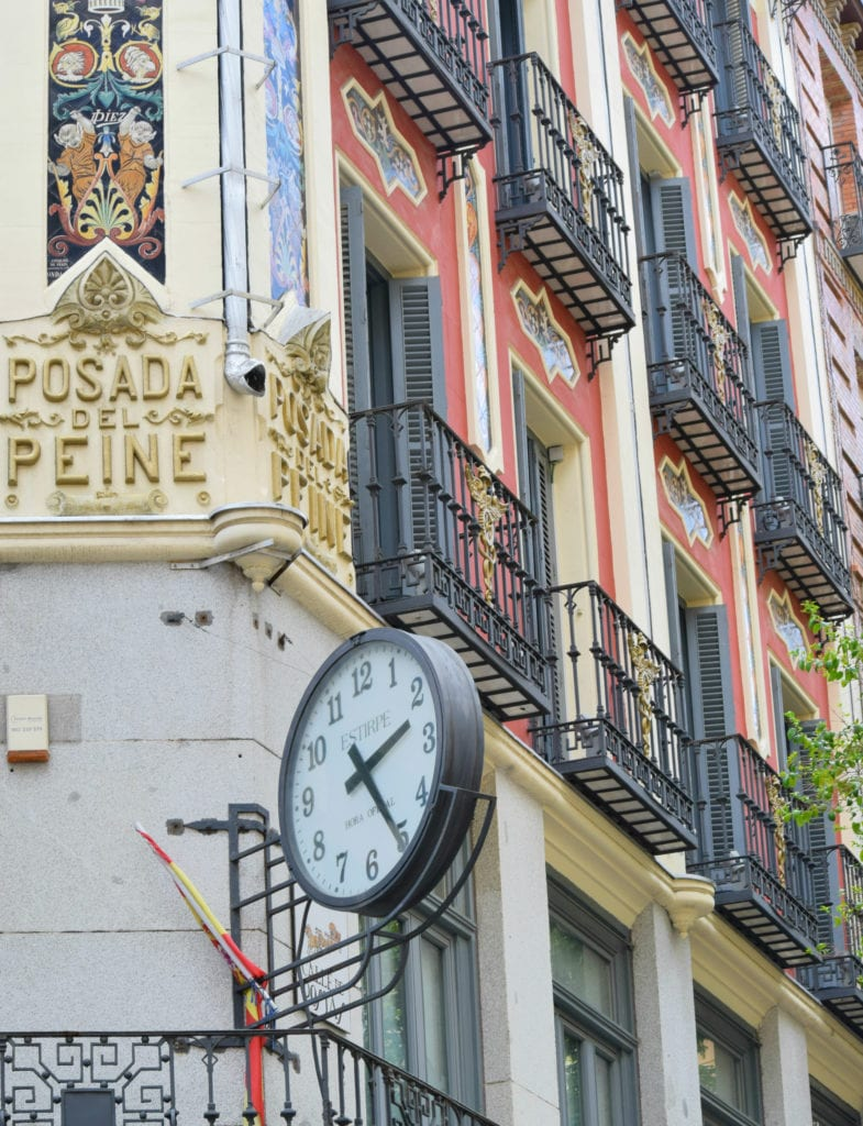 Clock attached to a red building with black wrought iron balconies in Madrid Spain--you'll see plenty of beautiful buildings like this during your 3 days in Madrid!