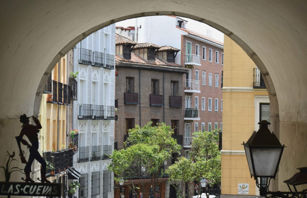 Photo of an arch in Madrid Spain with colorful buildings visible in the background