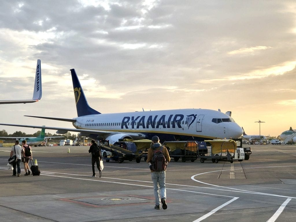 Ryanair plane parked on the tarmac with people boarding--you have to be extra careful to pack all your in flight essentials when taking a budget flight