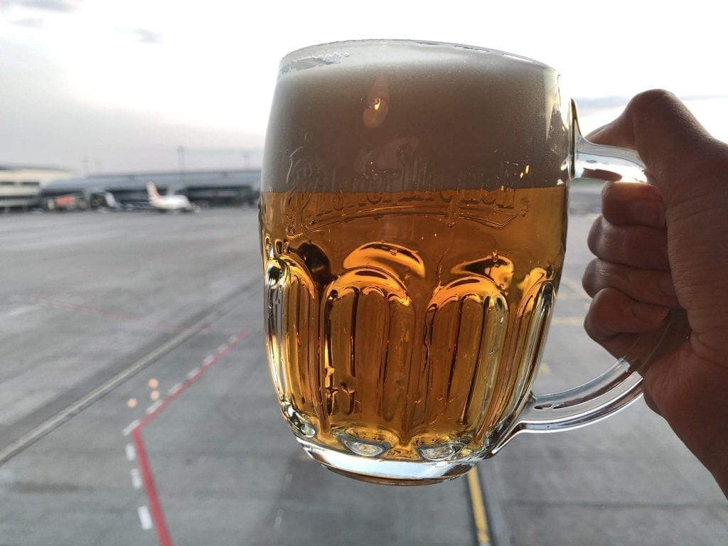 Czech Beer in Prague Airport being held against a window with planes in the background--beer definitely isn't a long haul flight essential, but it is tasty