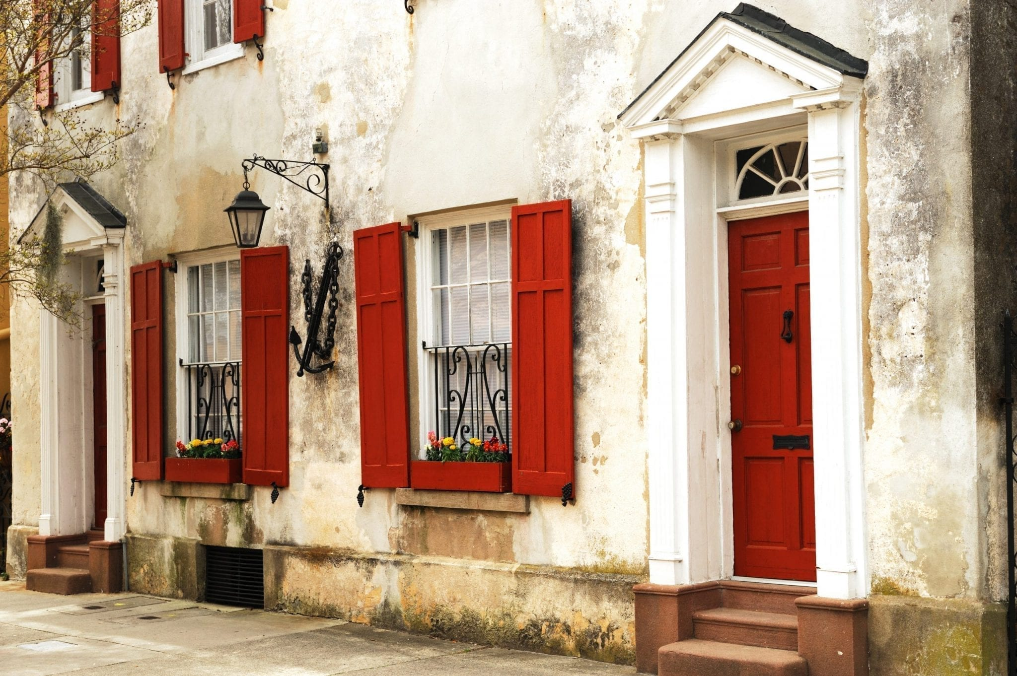 Photo of a white stucco building in charleston sc with red shutters. you'll see views like this when exploring what to do in charleston when it rains