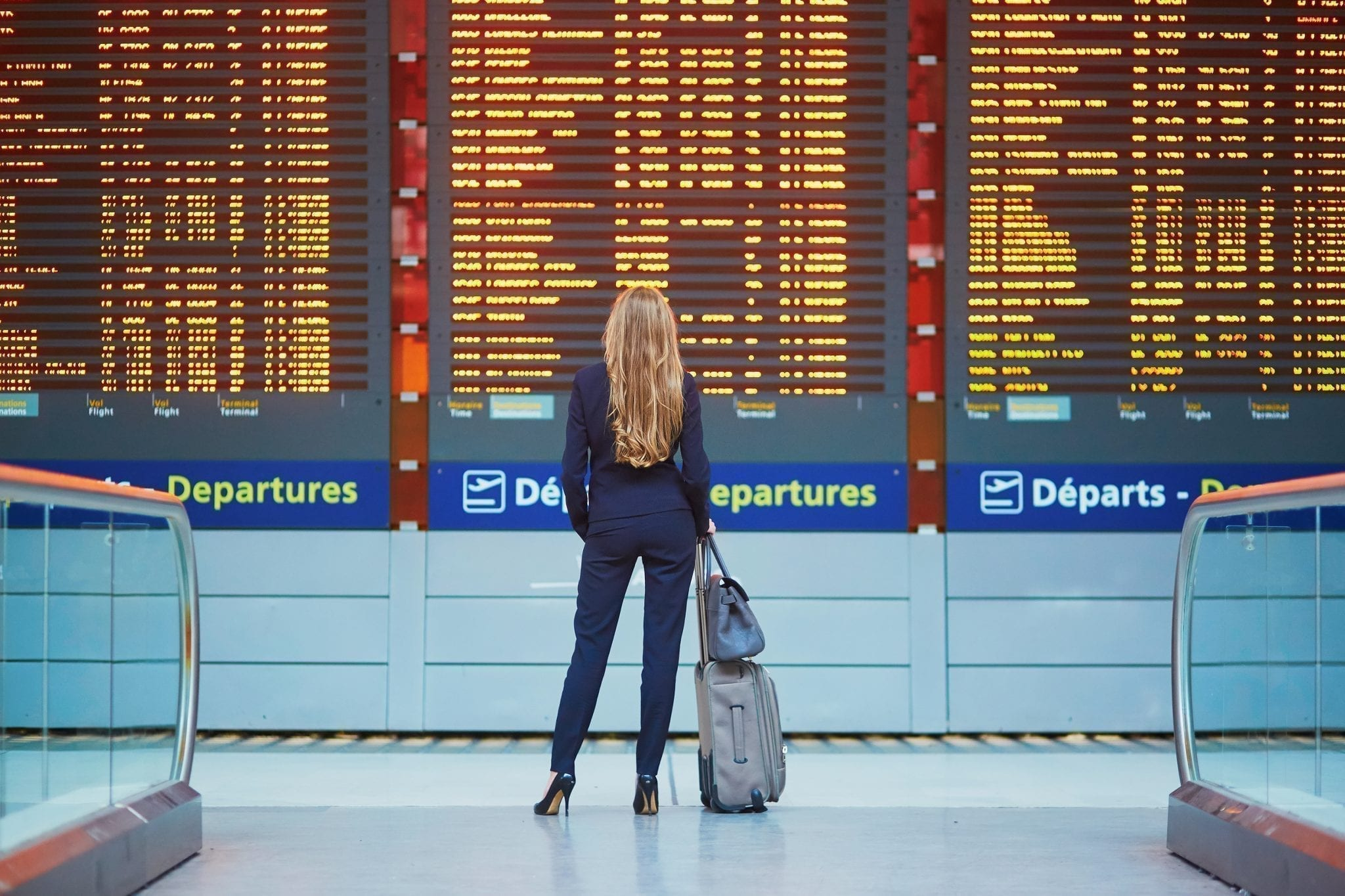 Woman with long blond hair standing in front of departures board in an airport with all travel essentials for the plane in her bag