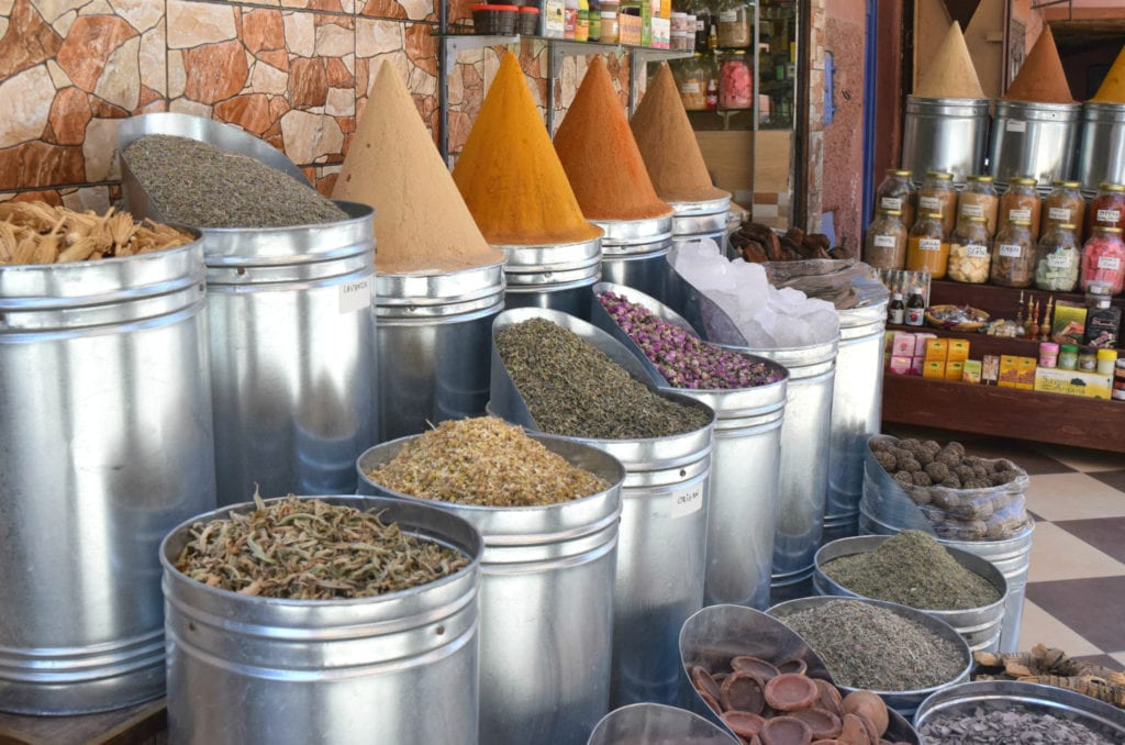 piles of spices in marrakech medina--spices are an affordable addition to trip to morocco costs and a morocco travel budget