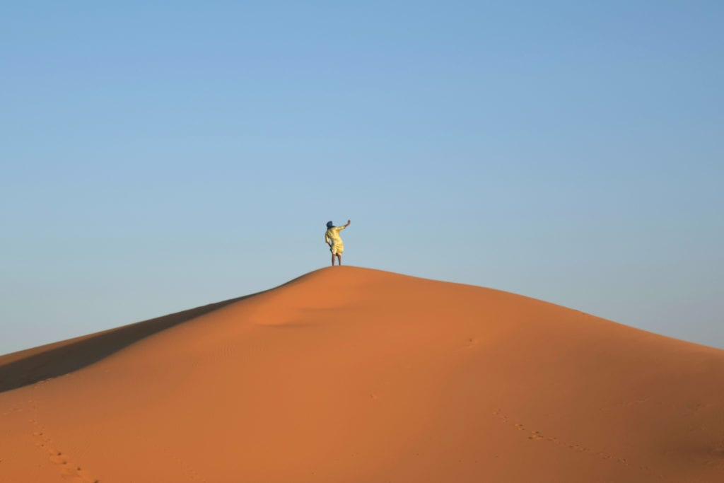 man taking a selfie from a sand dune during a sahara desert tour morocco