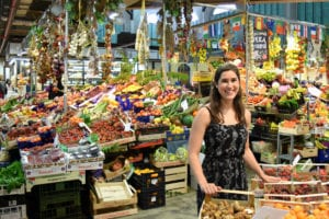 Kate Storm in a black sundress standing inside the Mercato Centrale, a must-see stop during your 2 day Florence itinerary