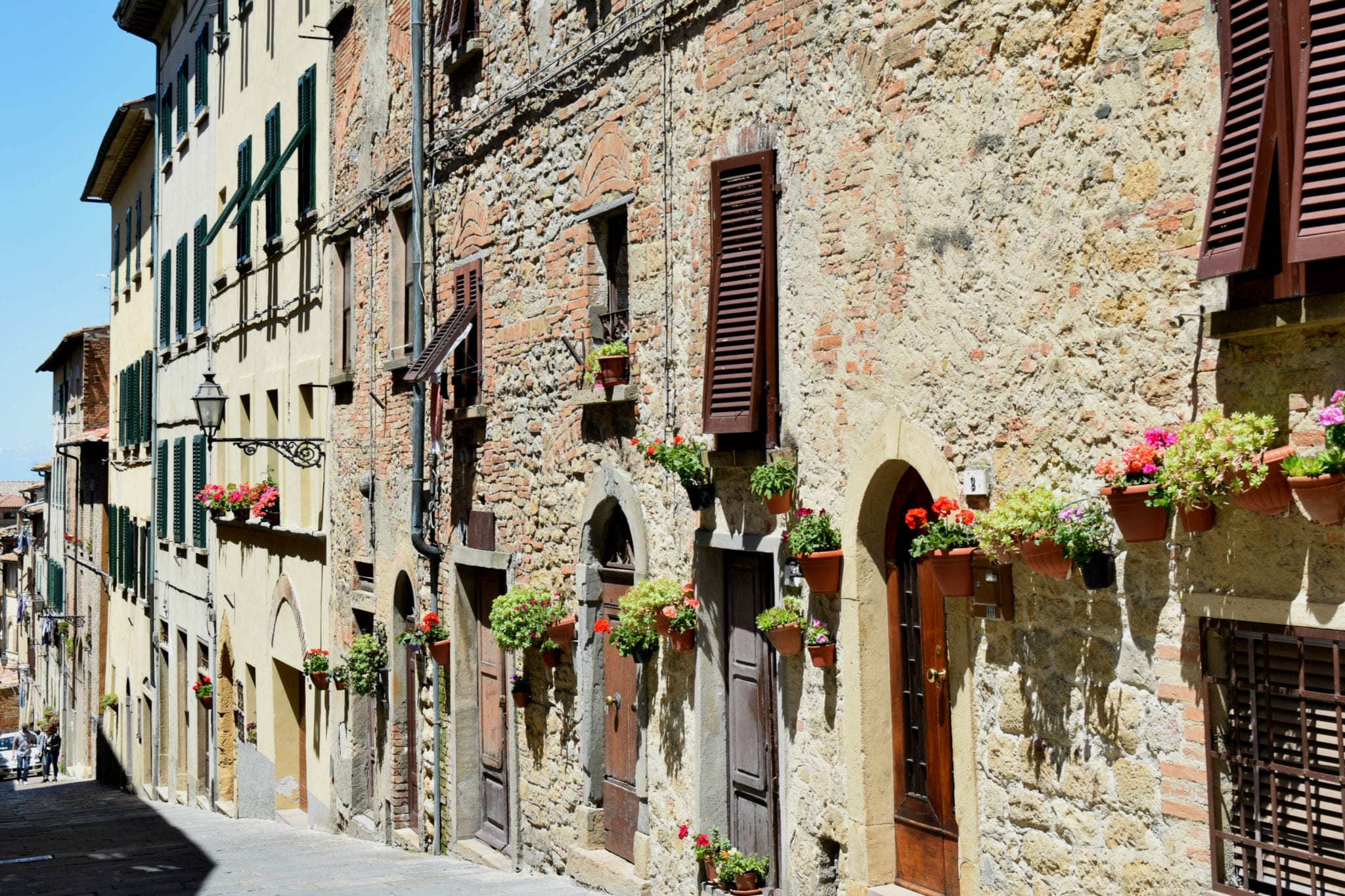 stone buildings with pots of flowers by the doors in tuscany
