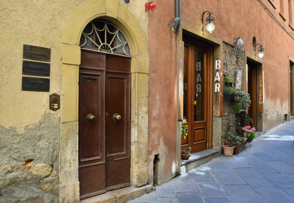 small street with closed doors and a coffee bar in volterra italy