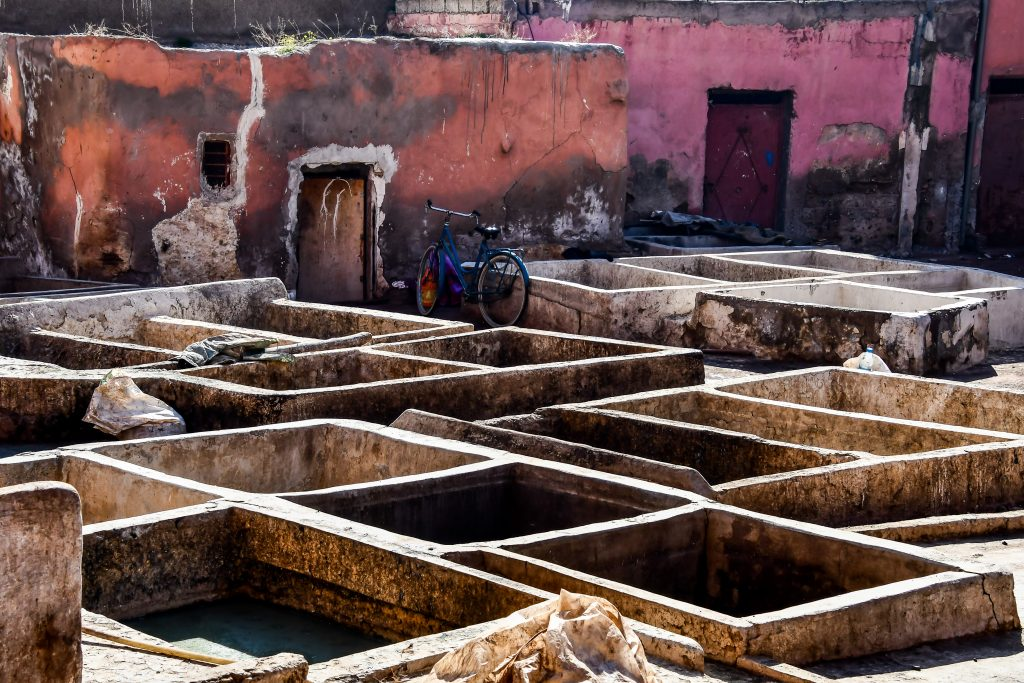 marrakech tannery as seen from above with pink and orange buildings in the background