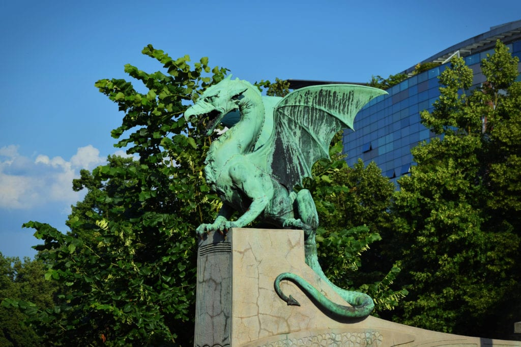 Green dragon statue perched on Dragon Bridge in Ljubljana Slovenia, one of the most fun cities in Europe to visit