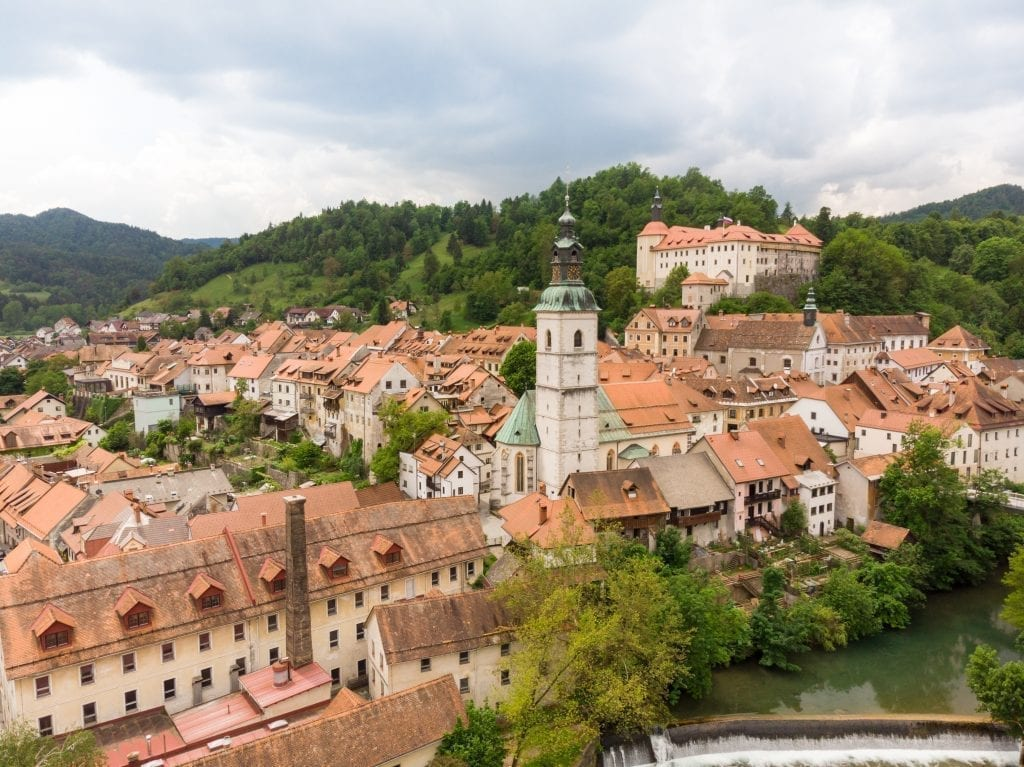 Cityscape of Skofja Loka from above with castle visible in the background, one of the best places to visit in Slovenia