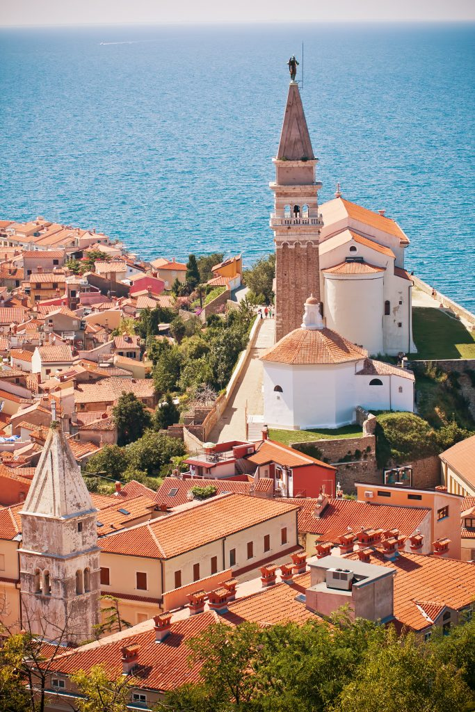 vertical photo of st georges church as seen from piran town walls