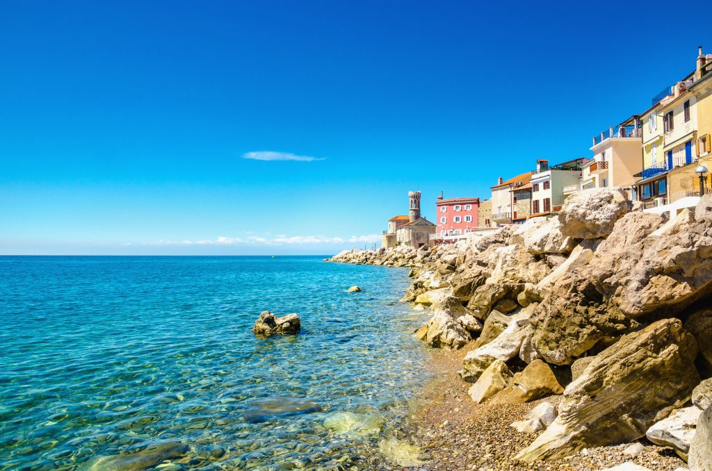 view of piran slovenia coastline with lighthouse in the background