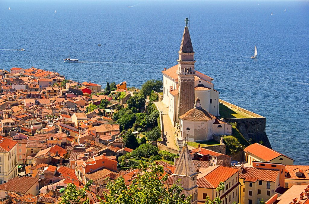 photo of piran slovenia from above with sailboat in the background