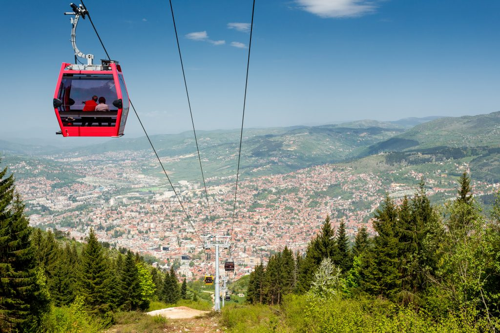 red mount trebevic cable car with sarajevo in the background, one of the fun things to do in sarajevo bosnia
