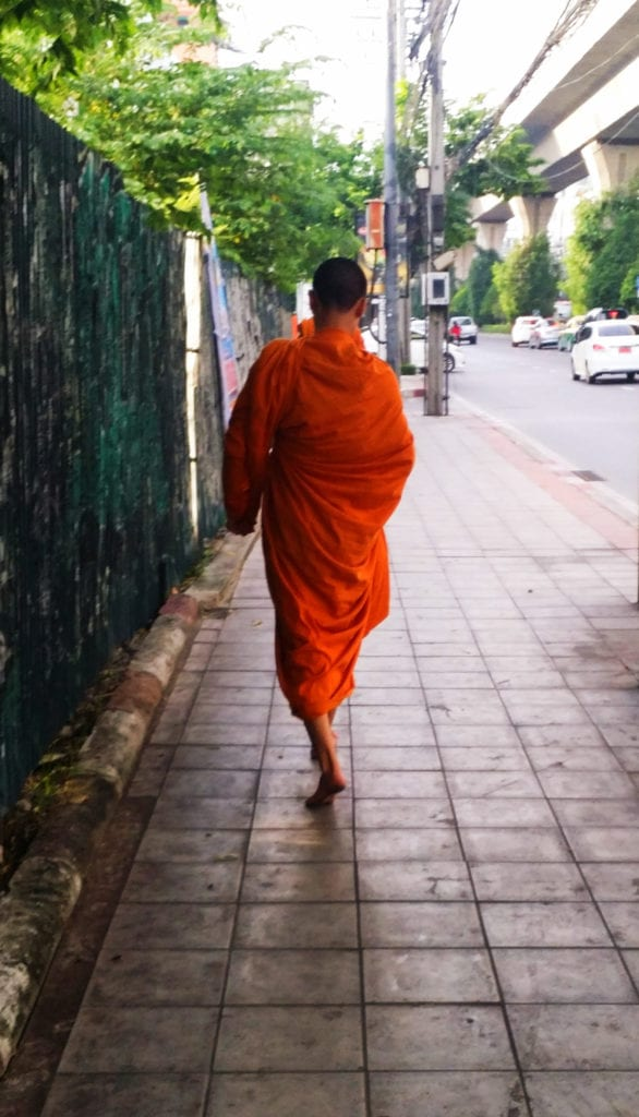 young monk in an orange robe that we saw walking down the street our first time in bangkok thailand