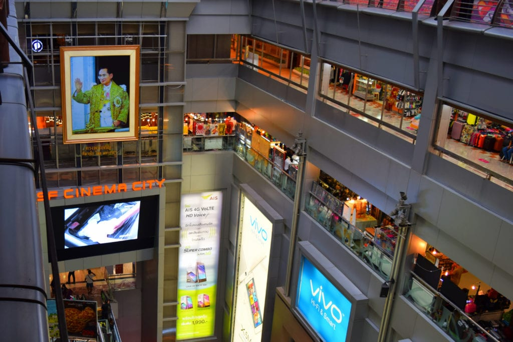 mbk shopping mall bangkok with portrait of king of thailand in it. one of our bangkok travel tips is to cool off at the malls