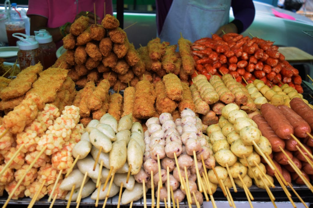 collection of fried food on a stick, some of the street food of bangkok