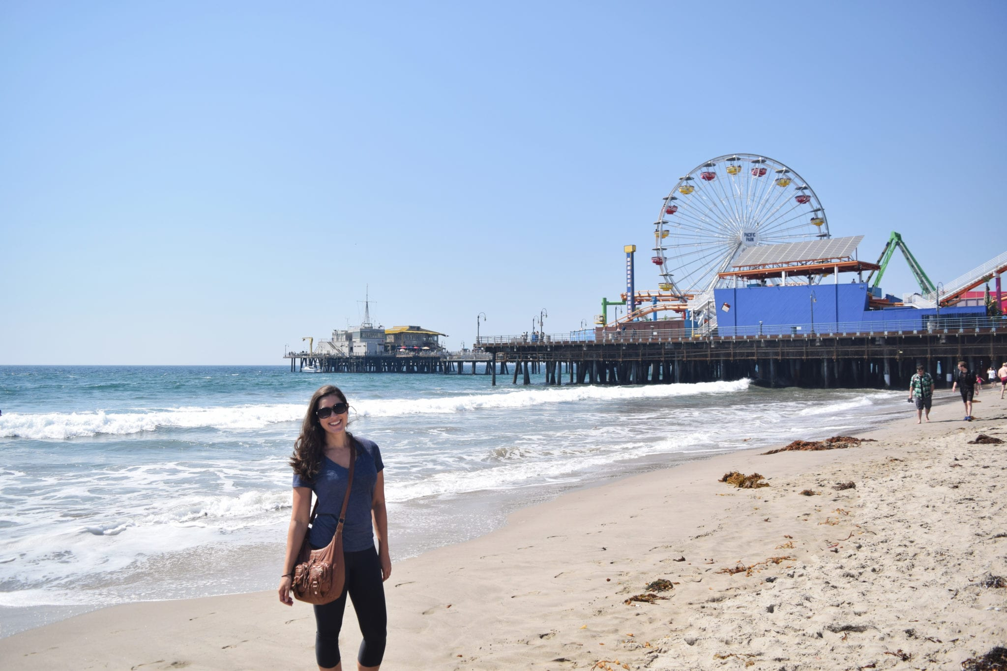 Kate Storm standing on the beach next to Santa Monica Pier is Los Angeles, California, the final destination of some of the most classic USA road trip itinerary ideas
