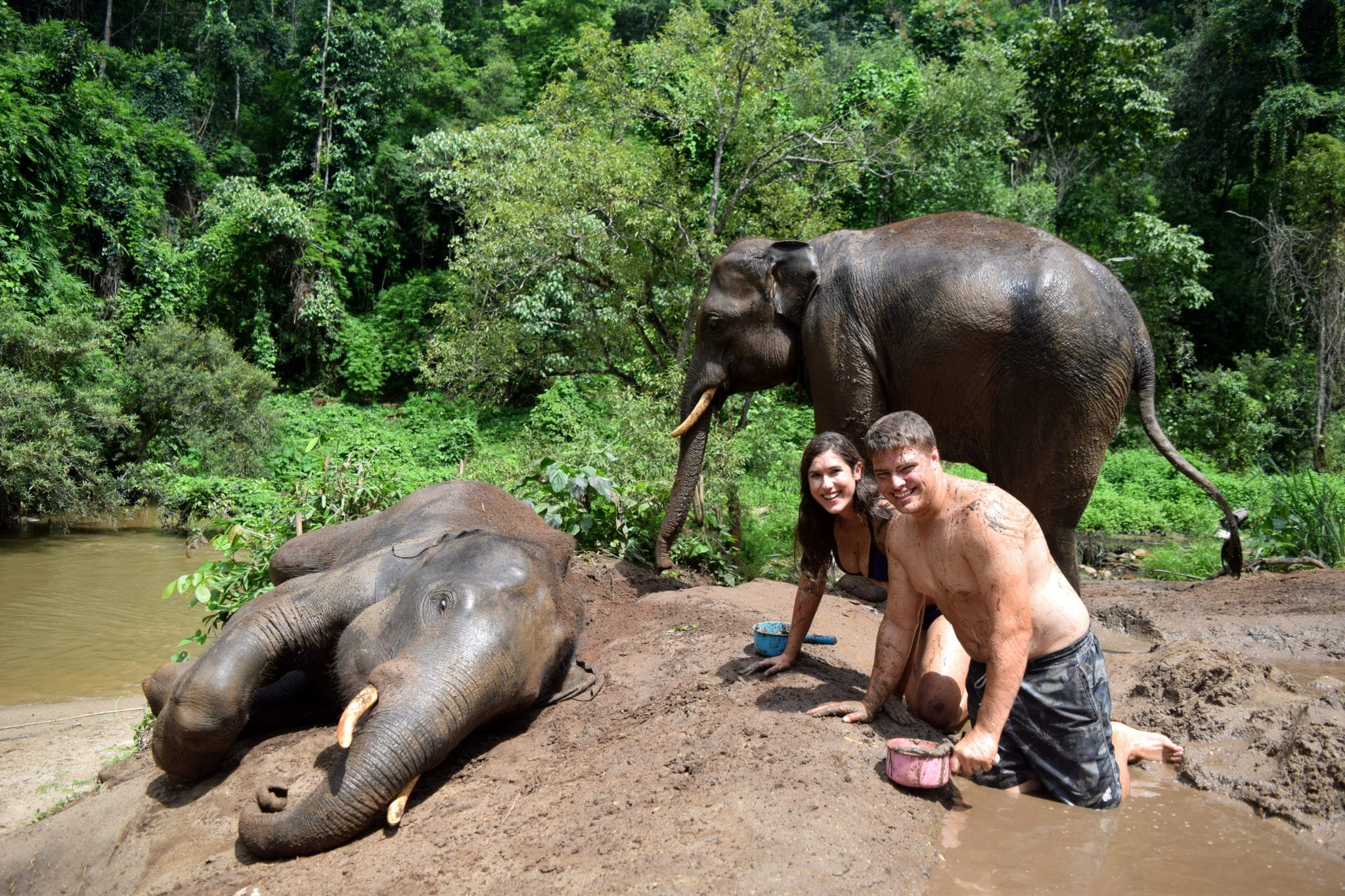 kate storm and jeremy storm with two elephants bathing them in thailand when backpacking the world