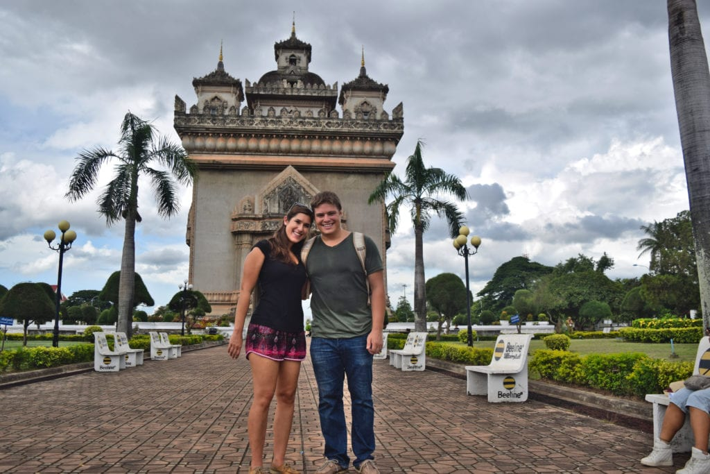 kate storm and jeremy storm standing in front of laos victory gate