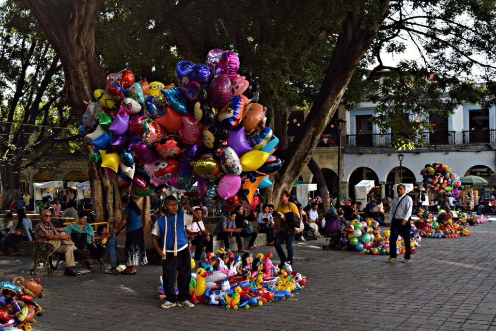 man selling balloons from a large bunch in the zocalo oaxaca de juarez