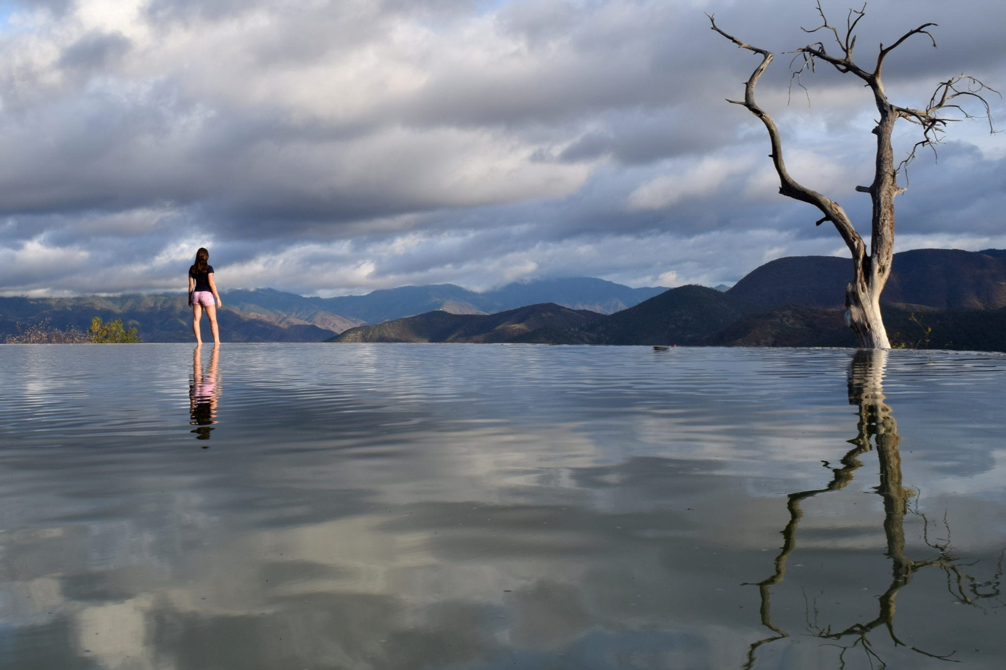 kate storm standing on the edge of a pool at hierve el agua, one of the most fun things to do in oaxaca mexico
