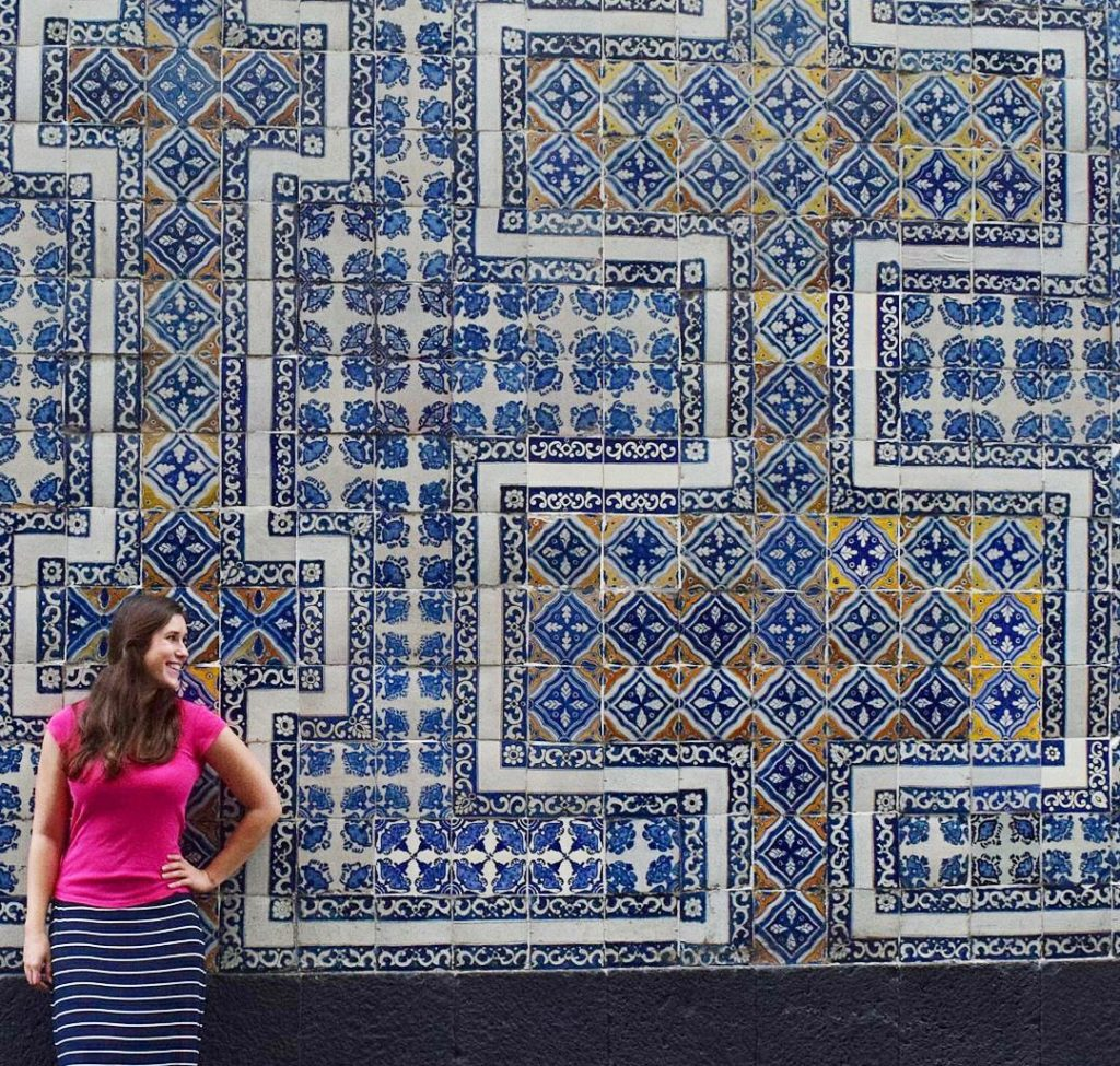kate storm in a pink shirt standing in front of the house of tiles during a mexico city itinerary