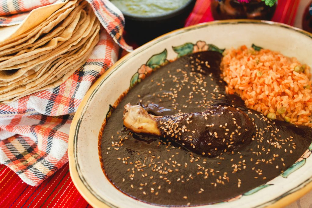 plate of mole with tortillas in the background, eating mole is one of the best things to do in oaxaca mexico