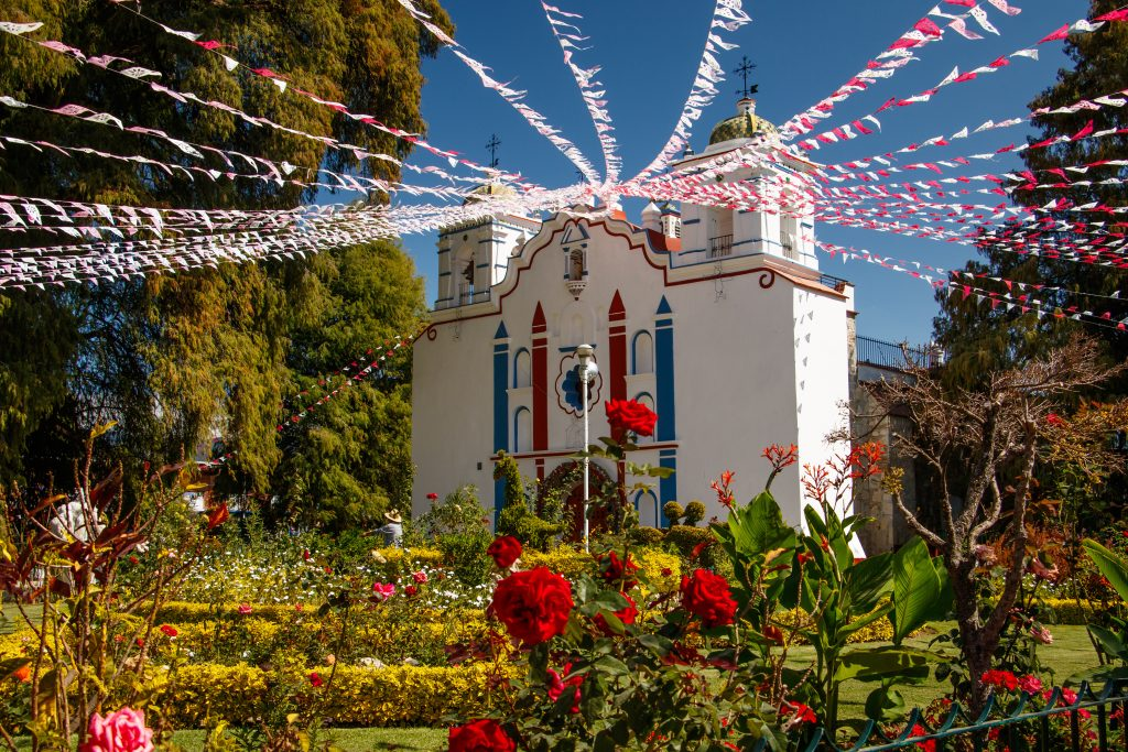 colorful church in the region of oaxaca mexico with flags dangling from it