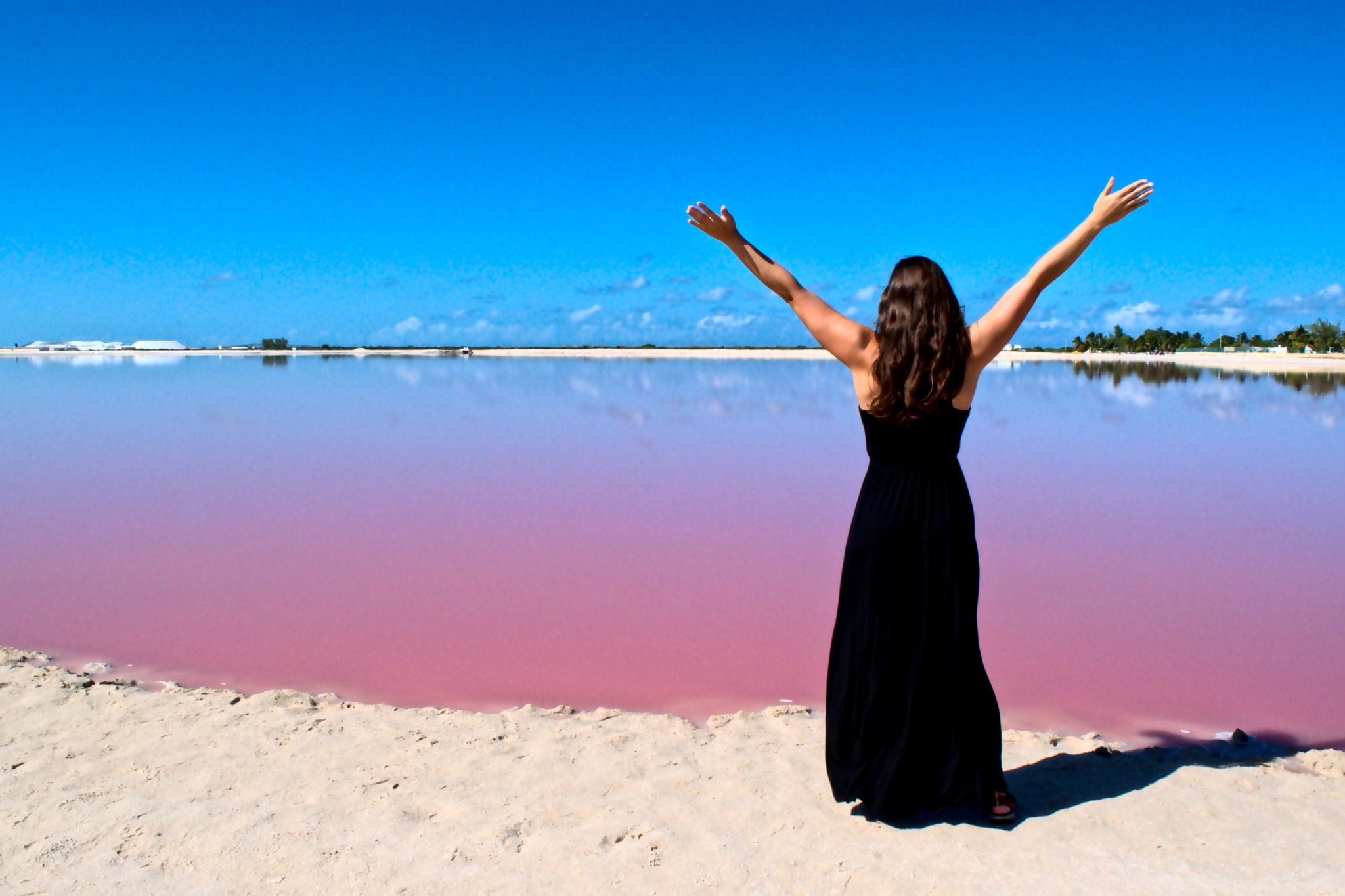 Kate Storm in a black maxi dress standing in front of one of the pink lakes las coloradas mexico
