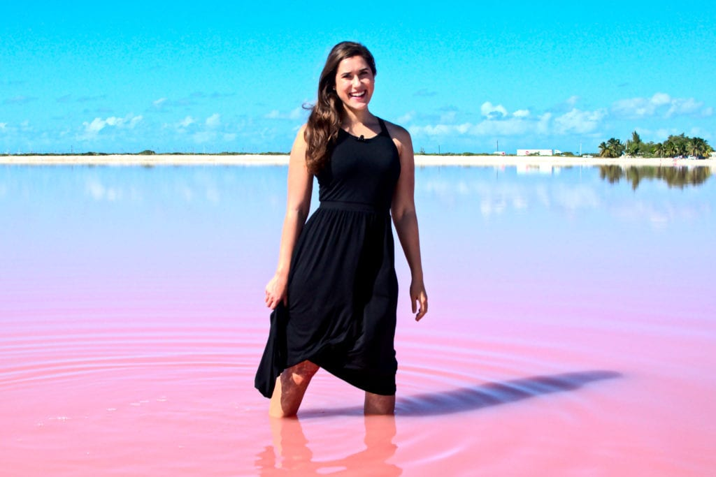 Kate Storm in a black dress standing in a pink lake in Mexico