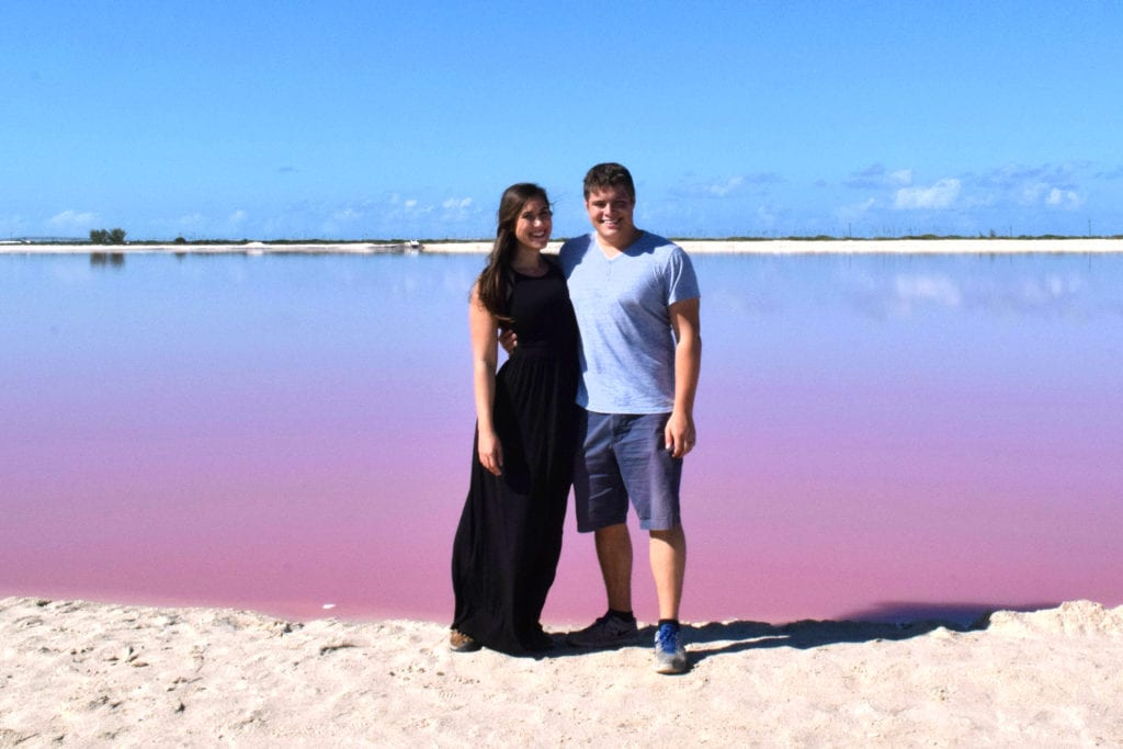 Kate Storm and Jeremy Storm standing in front of one a mexico pink lake las coloradas