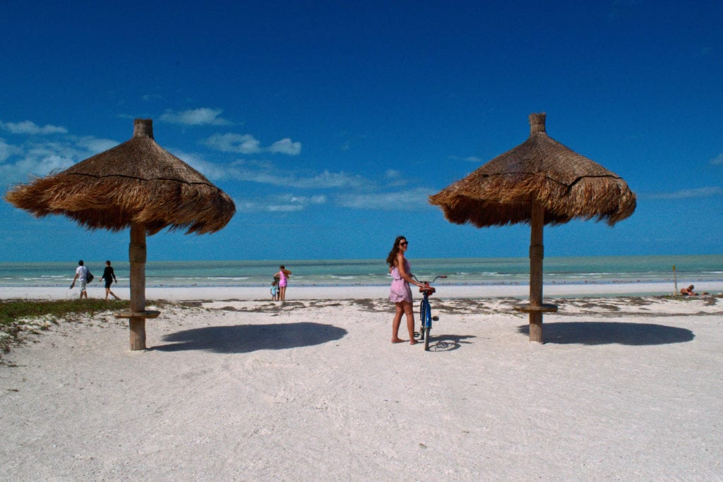 Kate storm standing with a bike on the beach on isla holbox mexico things to do