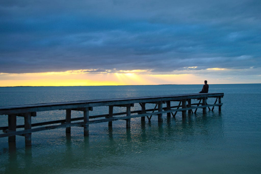 Jeremy storm sitting on a dock off of holbox island mexico when backpacking mexico