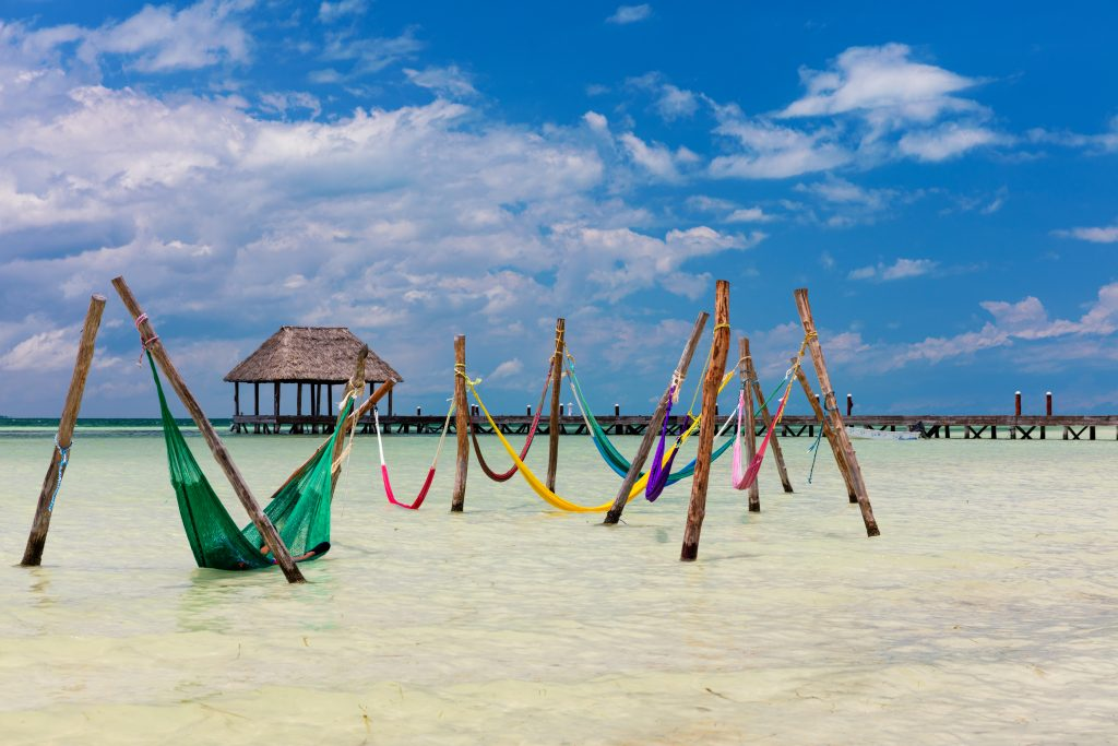 group of colorful hammocks in the water--relaxing here is among the best things to do on isla holbox mexico