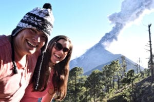 kate storm and jeremy storm in front of volcan de acatenango as a volcano erupts in the background