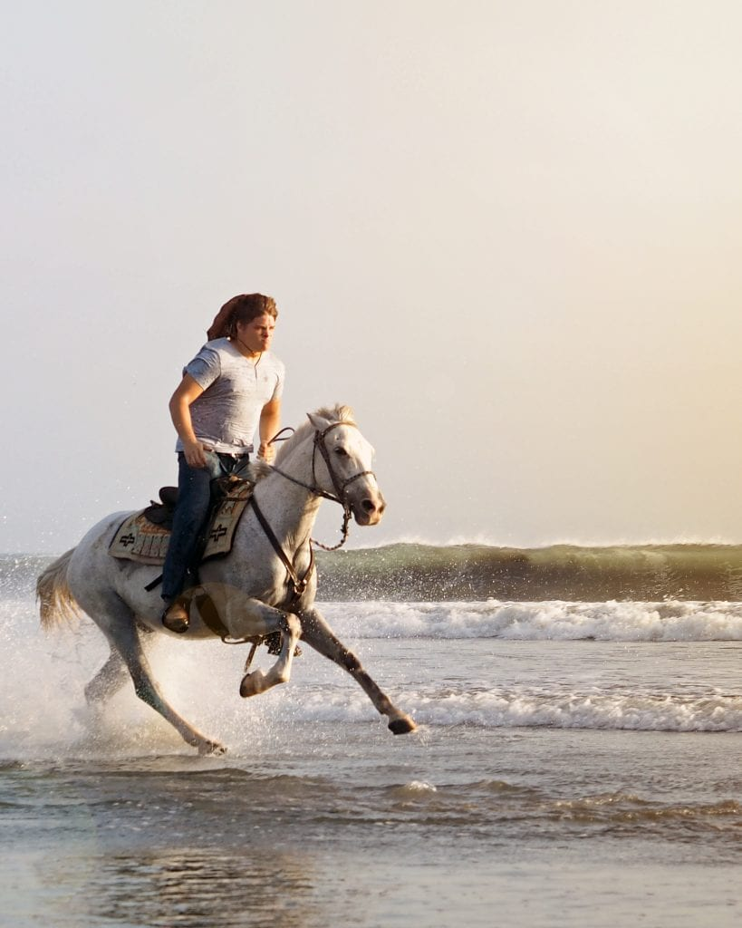 jeremy storm galloping a white horse down a beach in nicaragua